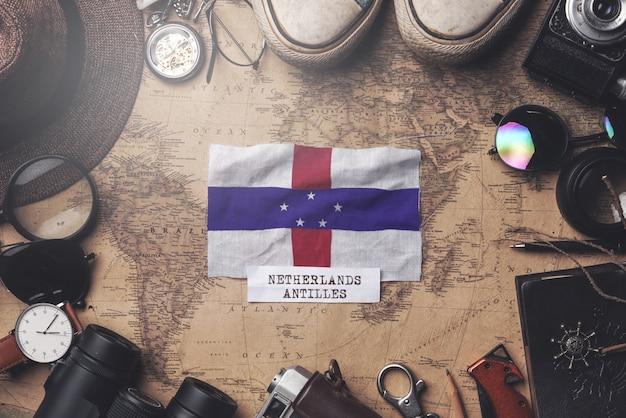 古いビンテージマップ上の旅行者のアクセサリーの間にオランダ領アンティル諸島の旗。オーバーヘッドショット