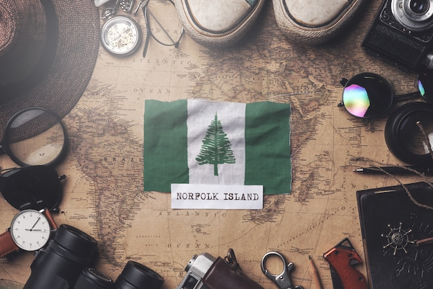 Флаг острова норфолк между аксессуарами путешественника на старой винтажной карте. верхний выстрел