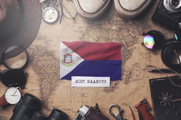 Флаг синт-мартена между аксессуарами путешественника на старой винтажной карте. верхний выстрел