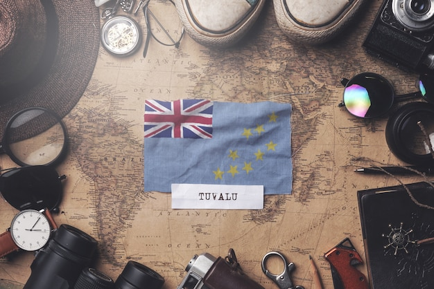 Флаг тувалу между аксессуарами путешественника на старой винтажной карте. верхний выстрел