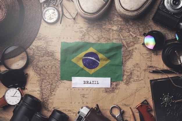 Флаг бразилии между аксессуарами путешественника на старой винтажной карте. верхний выстрел