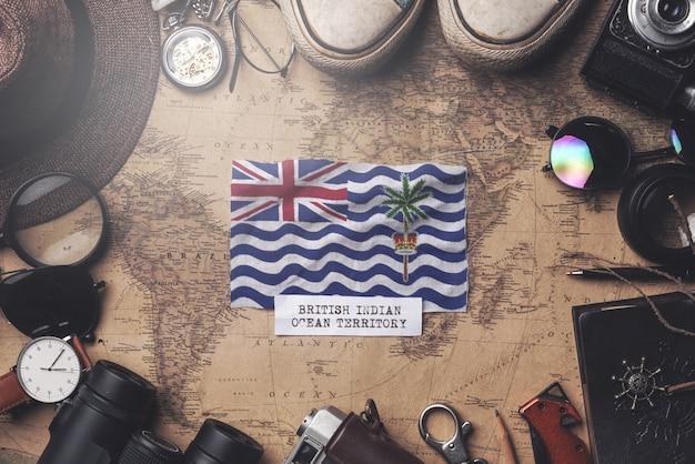 Флаг британской территории в индийском океане между аксессуарами путешественника на старой винтажной карте. верхний выстрел