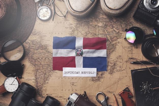 Флаг доминиканской республики между аксессуарами путешественника на старой винтажной карте. верхний выстрел