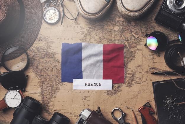 Флаг франции между аксессуарами путешественника на старой винтажной карте. верхний выстрел