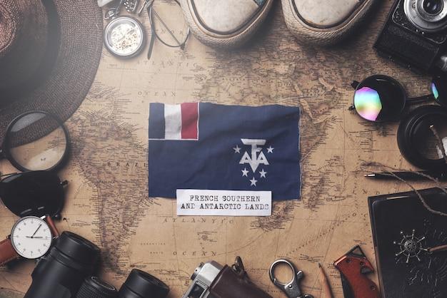 Французский южный флаг между аксессуарами путешественника на старой винтажной карте. верхний выстрел