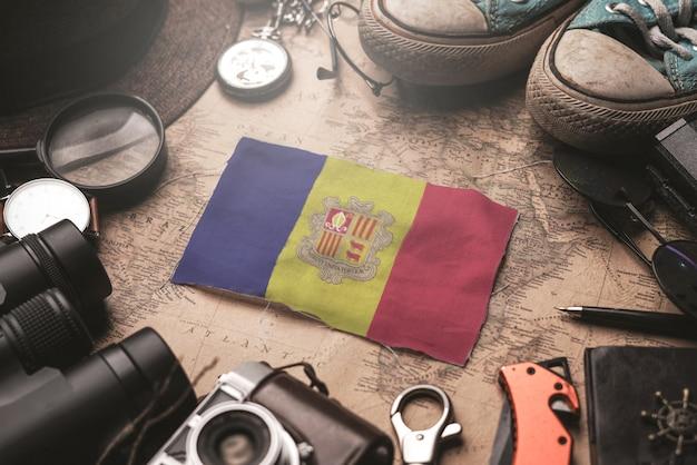 Флаг андорры между аксессуарами путешественника на старой винтажной карте. концепция туристического направления.