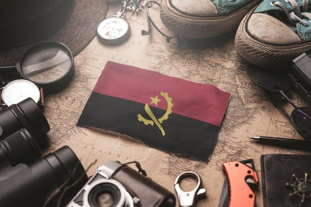 Флаг анголы между аксессуарами путешественника на старой винтажной карте. концепция туристического направления. концепция туристического направления.