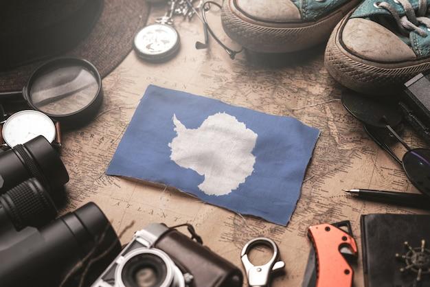 古いビンテージマップ上の旅行者のアクセサリー間の南極大陸の旗。観光地のコンセプト。