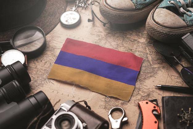 Флаг армении между аксессуарами путешественника на старой винтажной карте. концепция туристического направления.