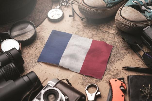 Флаг франции между аксессуарами путешественника на старой винтажной карте. концепция туристического направления.