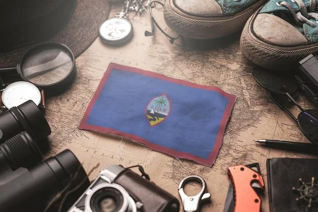 Флаг гуама между аксессуарами путешественника на старой винтажной карте. концепция туристического направления.