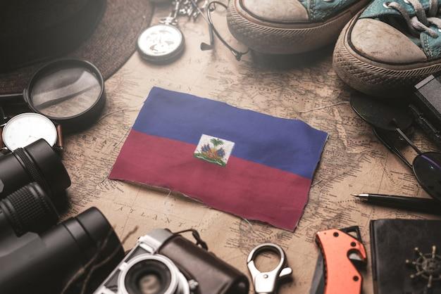 古いビンテージ地図上の旅行者のアクセサリーの間にハイチの国旗。観光地のコンセプト。