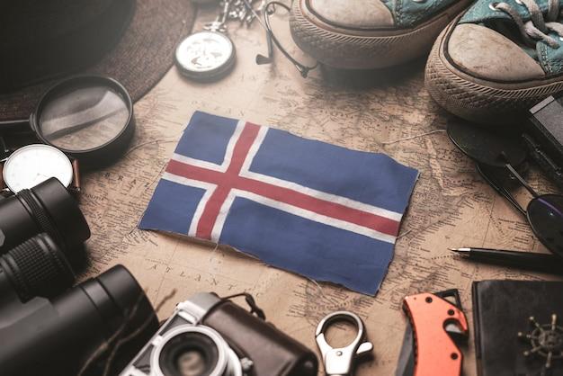 Флаг исландии между аксессуарами путешественника на старой винтажной карте. концепция туристического направления.