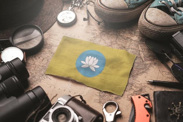 Флаг калмыкии между аксессуарами путешественника на старой винтажной карте. концепция туристического направления.