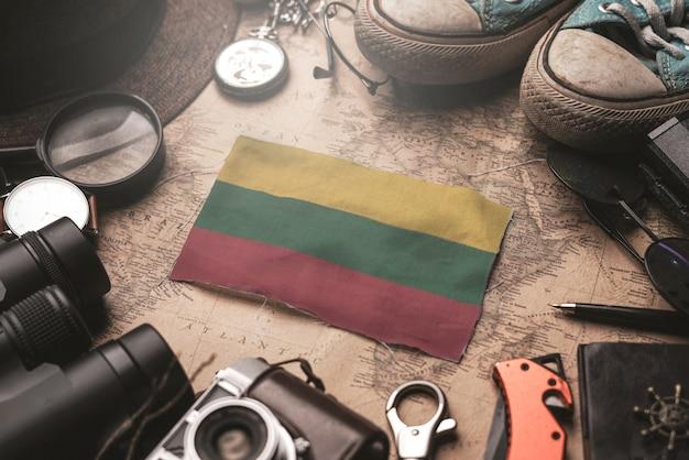 古いビンテージマップ上の旅行者のアクセサリー間のリトアニアの旗。観光地のコンセプト。