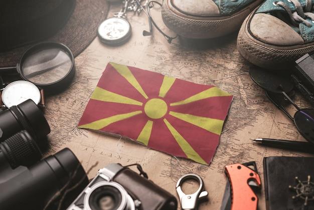 古いビンテージマップ上の旅行者のアクセサリーの間にマケドニア共和国の旗。観光地のコンセプト。