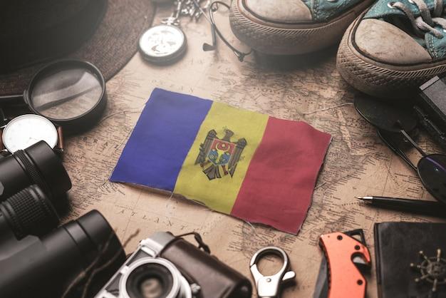 Флаг молдовы между аксессуарами путешественника на старой винтажной карте. концепция туристического направления.