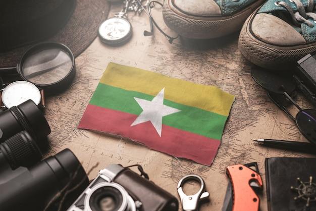 Флаг мьянмы между аксессуарами путешественника на старой винтажной карте. концепция туристического направления.