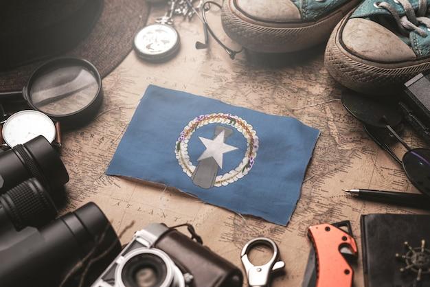 Флаг северных марианских островов между аксессуарами путешественника на старой винтажной карте. концепция туристического направления.