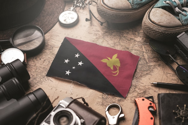 Флаг папуа-новой гвинеи между аксессуарами путешественника на старой винтажной карте. концепция туристического направления.