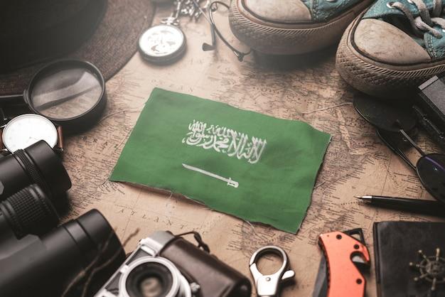 Флаг саудовской аравии между аксессуарами путешественника на старой винтажной карте. концепция туристического направления.