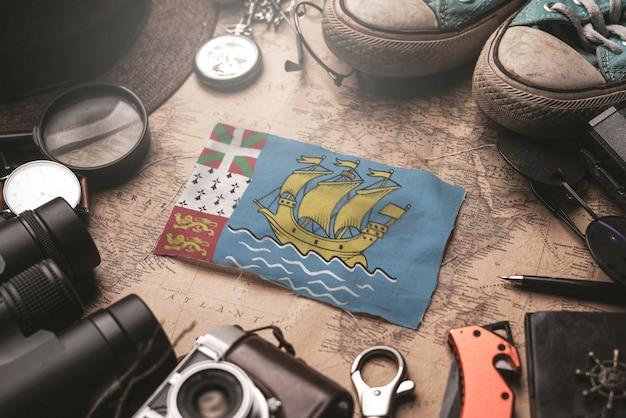 Флаг сен-пьер и микелон между аксессуарами путешественника на старой винтажной карте. концепция туристического направления.