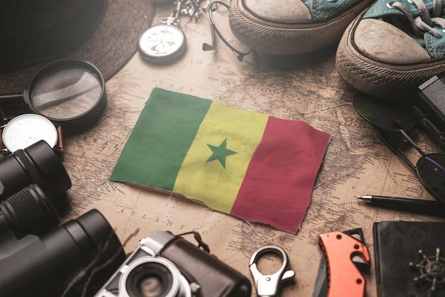Флаг сенегала между аксессуарами путешественника на старой винтажной карте. концепция туристического направления.