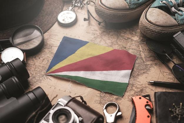 Флаг сейшельских островов между аксессуарами путешественника на старой винтажной карте. концепция туристического направления.