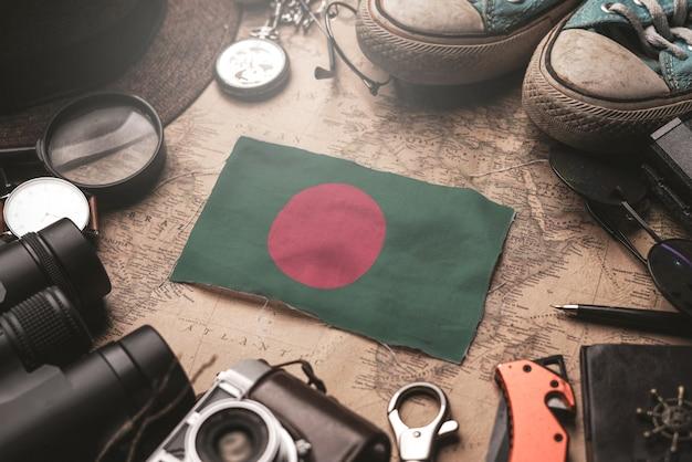 古いビンテージ地図上の旅行者のアクセサリーの間にバングラデシュの国旗。観光地のコンセプト。