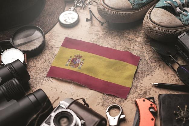 古いビンテージマップ上の旅行者のアクセサリーの間にスペイン国旗。観光地のコンセプト。
