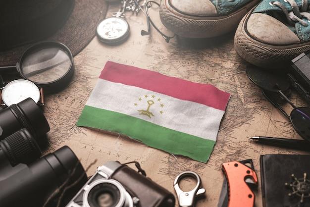 Флаг таджикистана между аксессуарами путешественника на старой винтажной карте. концепция туристического направления.