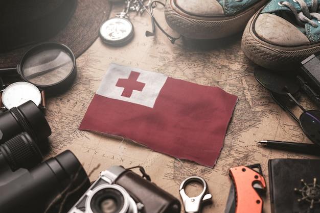 Флаг тонга между аксессуарами путешественника на старой винтажной карте. концепция туристического направления.