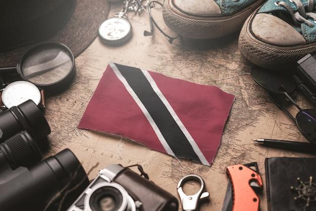 古いビンテージマップ上の旅行者のアクセサリーの間にトリニダード・トバゴの旗。観光地のコンセプト。