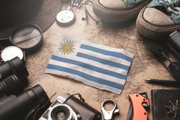 Флаг уругвая между аксессуарами путешественника на старой винтажной карте. концепция туристического направления.