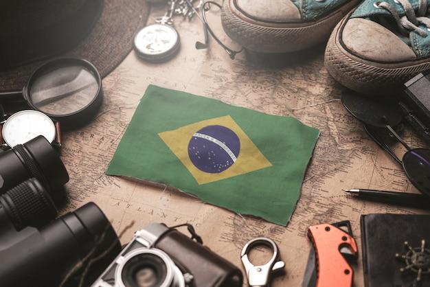 Флаг бразилии между аксессуарами путешественника на старой винтажной карте. концепция туристического направления.
