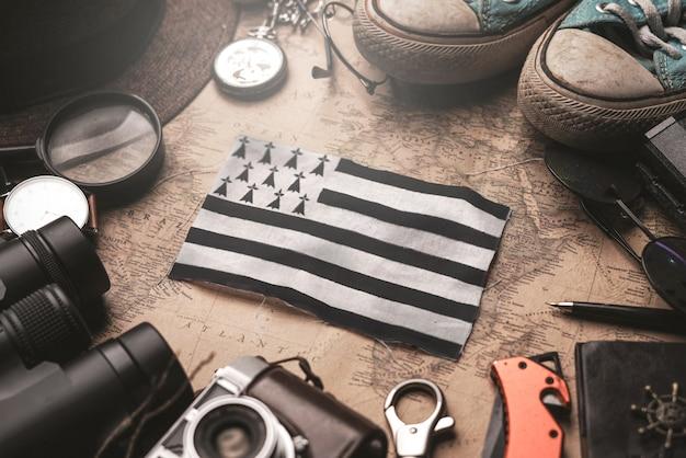 Флаг бретани между аксессуарами путешественника на старой винтажной карте. концепция туристического направления.