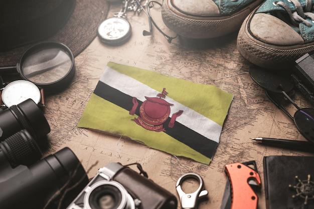 Флаг брунея между аксессуарами путешественника на старой винтажной карте. концепция туристического направления.