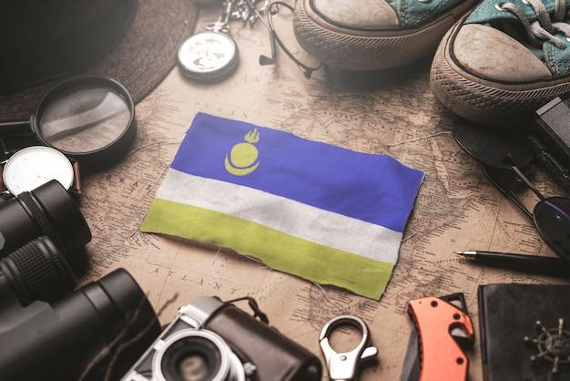 Флаг бурятии между аксессуарами путешественника на старой винтажной карте. концепция туристического направления.