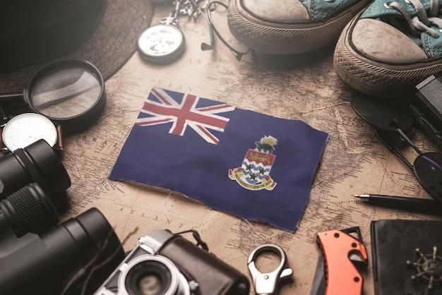 Флаг каймановых островов между аксессуарами путешественника на старой винтажной карте. концепция туристического направления.