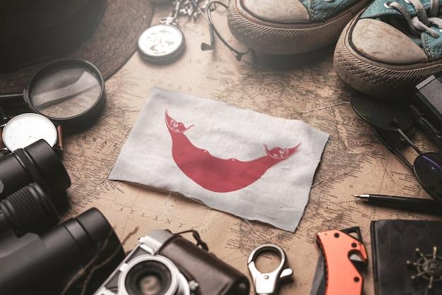 Флаг острова пасхи между аксессуарами путешественника на старой винтажной карте. концепция туристического направления.