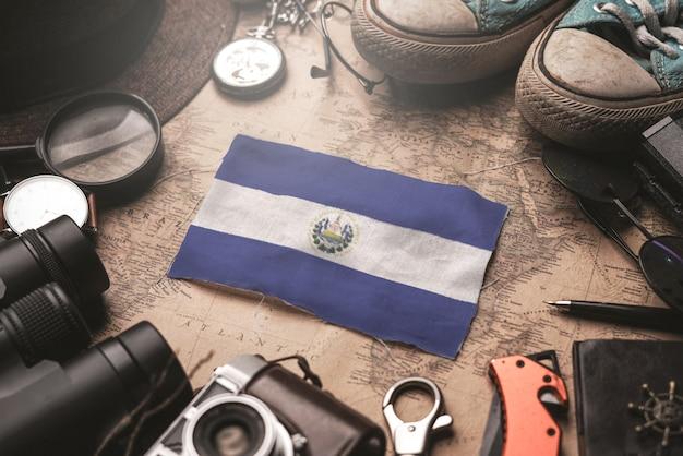 古いビンテージ地図上の旅行者のアクセサリーの間にエルサルバドルの国旗。観光地のコンセプト。