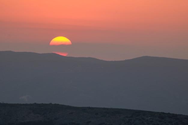 山に沈む夕日、山の後ろに沈む夕日。