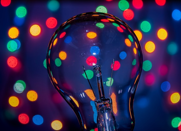 色とりどりのライトの背景上の電球