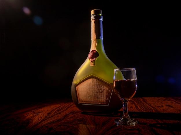 低光の中でガラスが付いている酒瓶