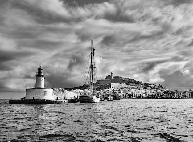 Городской пейзаж над водой дальт вила и залив города ибица, балеарские острова, испания. черно-белая фотография