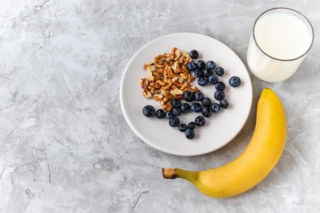 Здоровый завтрак, черника, орех, банан, стакан молока на цементе