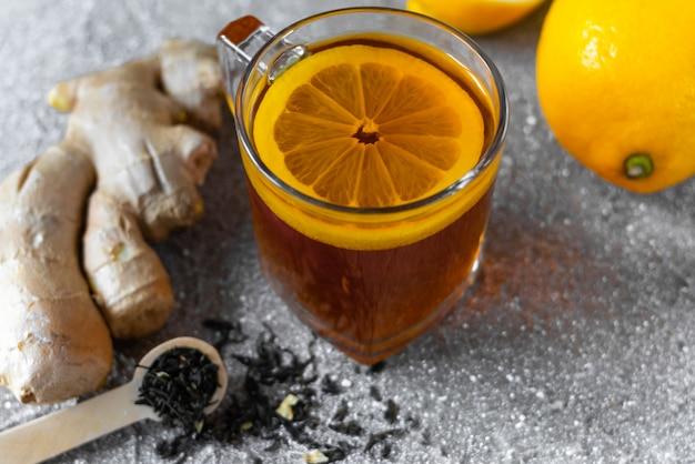 Чай с лимоном, корнем имбиря и чайной ложкой на сером фоне для профилактики гриппа. вид сверху