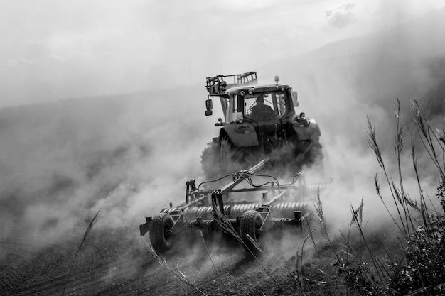 ほこりだらけの畑を耕すトラクター