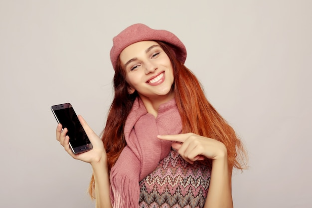 ピンクの服を着て、スマートフォンを使用して若い女性の肖像画