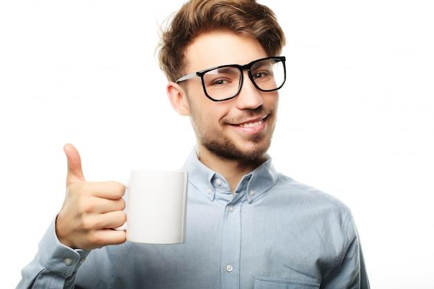 Красивый мужчина в повседневной одежде, держа чашку